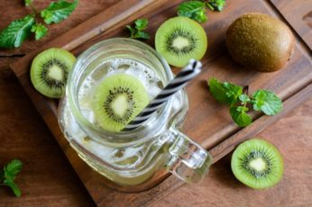 kiwi soda and mint in a glass on a wooden background, Top view